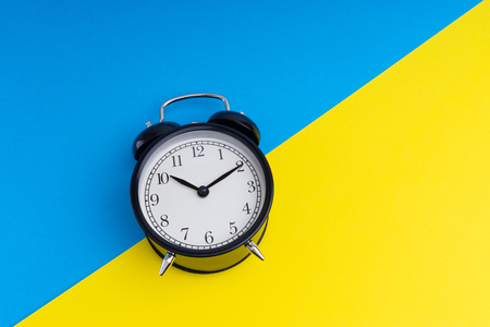 Photo for Black vintage alarm clock on a blue and yellow background with selective focus - Royalty Free Image