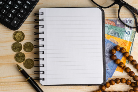 Foto de Calculator, rosary, coins, banknotes, book, spectacle and pen on wooden background. Selective focus and crop fragment. Copy space concept - Imagen libre de derechos