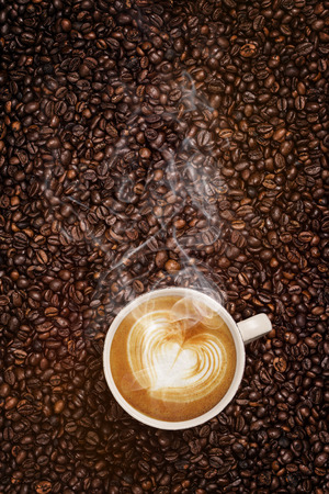 steaming cup of coffee with heart made of frothy milk standing on top of roasted coffee beans