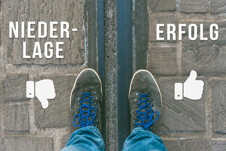 Reaching a crossroads having to choose between niederlage and erfolg meaning failure and success symbolized by two feet standing on two different colors with arrows on pathway from above