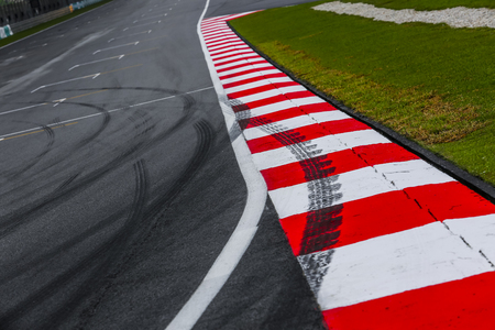 Photo pour Asphalt red and white kerb of a race track detail with tire marks. Motorsports racing circuit close up.  - image libre de droit