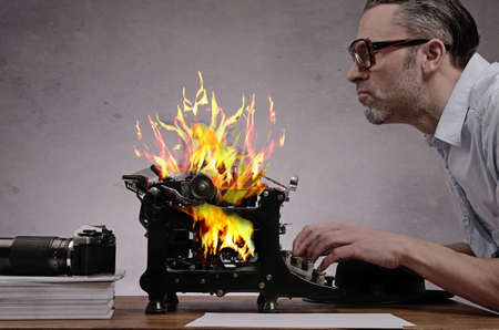 Photo pour Editor with an old typewriter working on a hot story - image libre de droit