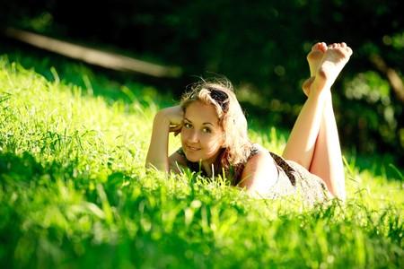 beautiful girl laying in grass on sunny meadow