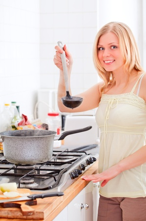 cute young woman cooking in bright kitchen