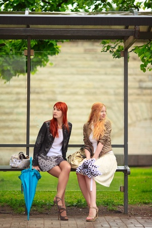 two girls at bus stop, rainy day