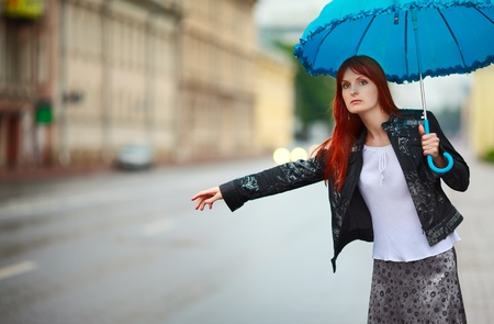 redhead girls with umbrella hitch-hiking at rainy day
