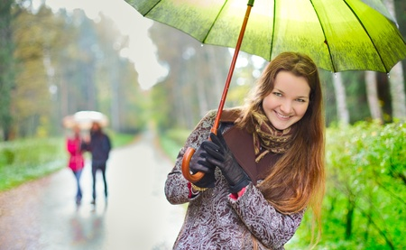 laughing girl and walking couple under rainfall in autumn park