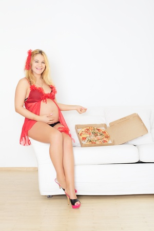 pregnant woman sitting on sofa with pizza