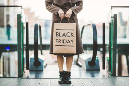 Photo pour Beautiful elagance woman holding Black Friday paper bag in shopping mall - image libre de droit