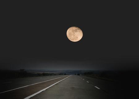 Highway passing through desert in moon light