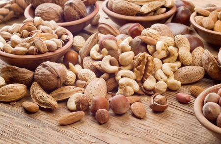 Photo for Nuts mix, with almond, cashews, pistachios, hazelnuts on wood background - Royalty Free Image