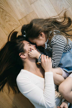 Foto de Mom playing with daughter at home laying on the floor - Imagen libre de derechos