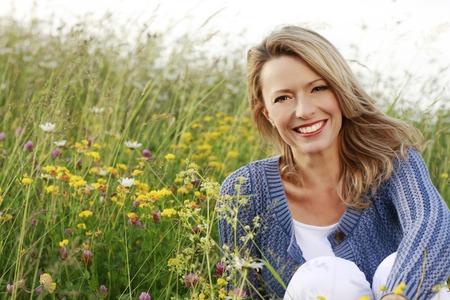 Foto de Happy middle aged woman in wild flower field - Imagen libre de derechos