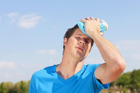 Foto de Young man with icepack on his foreheat in the summer heat - Imagen libre de derechos