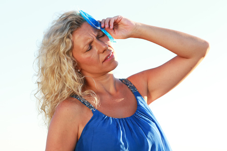 Photo for Mature woman with ice pack in summer heat outdoor - Royalty Free Image