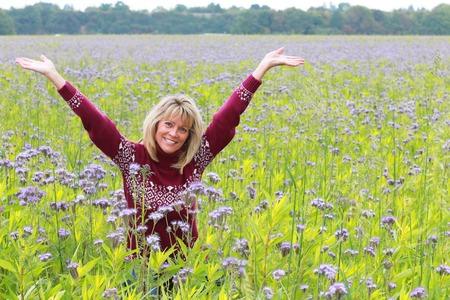 Foto de Mature woman in autmn with pullover  in flower field with raised arms - Imagen libre de derechos