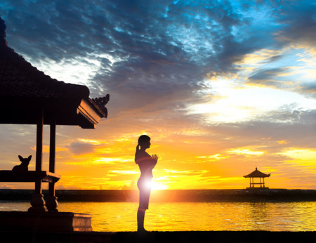 Photo for Silhouette of young woman practising yoga meditation in standing full lotus position near gazebo or   pagoda at beach in Bali during sunrise or sunset with her dog. Sanur beach has many gazebo facing the ocean.  - Royalty Free Image