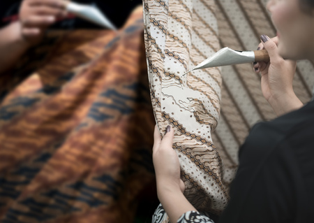 Foto de Batik painting and waxing traditional making process with hand dyed. Batik pattern,   symbol, clothing and fabric has become a world heritage by UNESCO in 2009. - Imagen libre de derechos