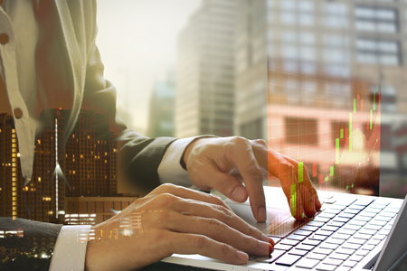 Foto de Double exposure of businessman using the laptop with stock market or financial graph for financial investment concept on blurred building background. - Imagen libre de derechos