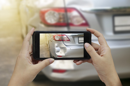 Photo for Hand holding smart phone take a photo at The scene of a car crash, car accident for insurance. - Royalty Free Image