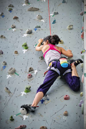 Asian girl wearing harness and belaying rope, climbing on a very high rock climbing wall