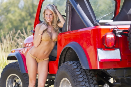Photo for Beautiful blonde model posing with a car in a field - Royalty Free Image