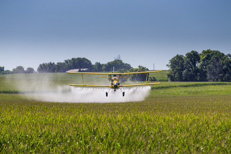 Foto de A crop duster applies chemicals to a field of vegetation. - Imagen libre de derechos