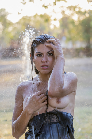 Photo for A beautiful hispanic brunette model cooling off on a summer day - Royalty Free Image