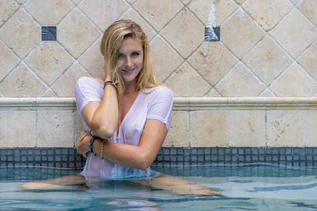 Photo pour A beautiful blonde bikini model enjoys a day by by the pool - image libre de droit