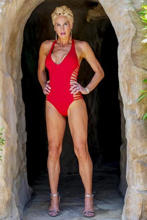 Foto de A beautiful mature blonde bikini model poses outdoors near a swimming pool. - Imagen libre de derechos