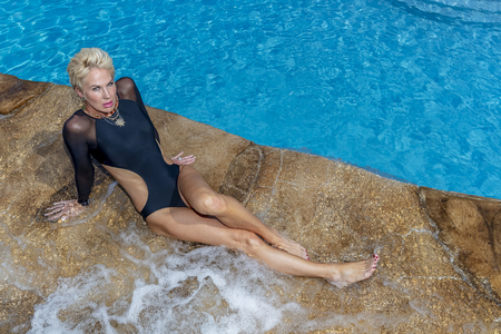 Photo for A beautiful mature blonde bikini model poses outdoors near a swimming pool. - Royalty Free Image