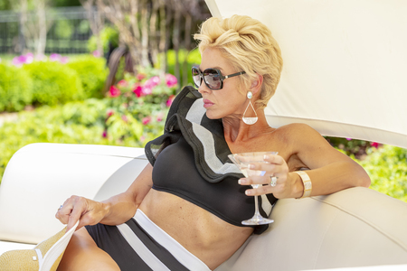 Photo for A beautiful mature blonde bikini model poses outdoors near a swimming pool. - Royalty Free Image