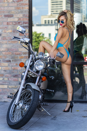 Photo for A gorgeous Brazilian Blonde bikini model poses with a motorcycle on the city streets - Royalty Free Image