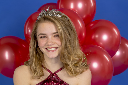 Foto de A beautiful blonde teenage model posing in a tiara and red balloons in front of the camera in a studio environment - Imagen libre de derechos