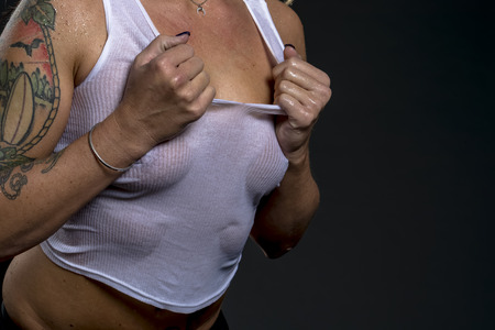 Foto de A beautiful blonde lingerie model ripping off her shirt exposing her breasts - Imagen libre de derechos