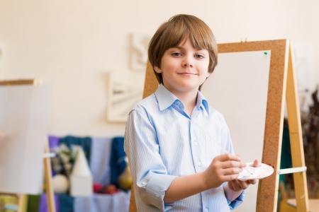 portrait of a boy standing next to his easel, a drawing lesson