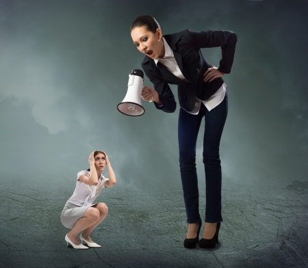 Foto de Business woman yelling at a small woman sitting on the ground, the concept of aggression - Imagen libre de derechos