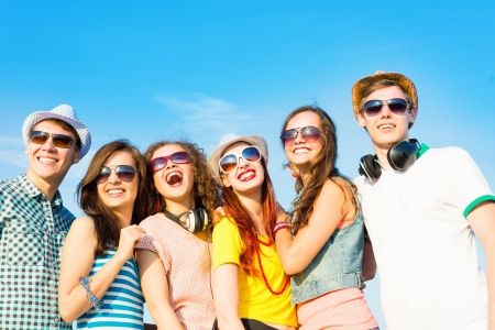 Foto per group of young people wearing sunglasses and hats hugging and standing in a row, spending time with friends - Immagine Royalty Free