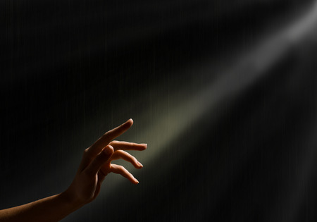 Photo pour woman s hand reaches for the light rays, conceptual image of striving for freedom - image libre de droit