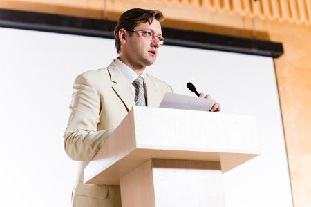male speaker stands behind a podium on the stage and looking into the hall