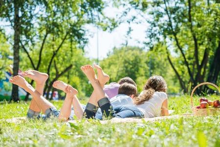 Foto de Young happy family lying in park barefoot - Imagen libre de derechos
