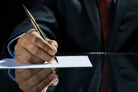 Photo pour Close up of businessman sitting at table and signing document - image libre de droit
