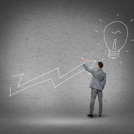 Rear view of businessman drawing increasing graph