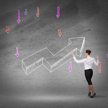 Rear view of businesswoman drawing increasing graph