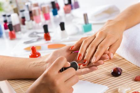 Photo pour Woman in salon receiving manicure by nail beautician - image libre de droit