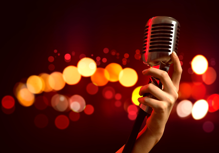 Photo for Close up of female hand on blurred background holding microphone - Royalty Free Image