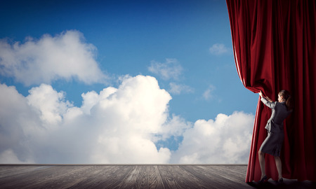 Photo for Young woman in business suit opening color curtain of stage - Royalty Free Image