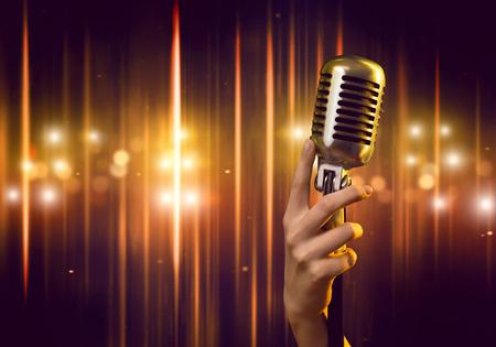 Foto de Close up of female hand on blurred background holding microphone - Imagen libre de derechos