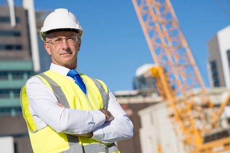 Foto de Confident construction engineer in hardhat with arms crossed on chest - Imagen libre de derechos