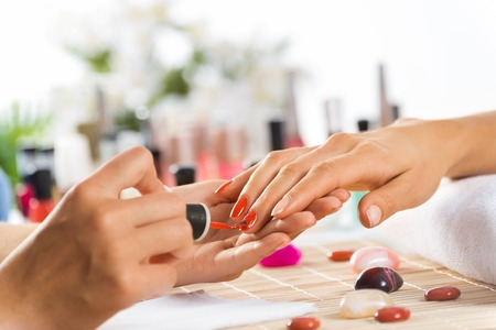 Photo for Woman in salon receiving manicure by nail beautician - Royalty Free Image